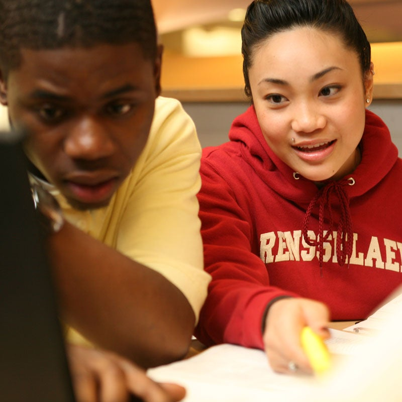 Two students working on a laptop as part of a group project.