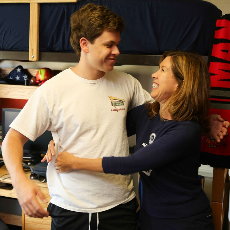 Mother and son embrace in dorm room during Family Weekend